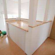階段を上ると、吹き抜け脇にディスプレイスペース設置。 天板の下は収納スペースとしても活用できます。